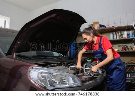 Young female mechanic repairing car in body shop #746178838