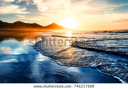 Amazing beach sunset with endless horizon and lonely figures in the distance #746217688