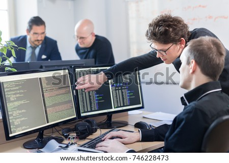 Startup business and entrepreneurship problem solving. Young AI programmers and IT software developers team brainstorming and programming on desktop computer in startup company share office space. #746228473