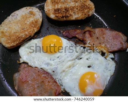two fried eggs with two slices of back pork bacon in a non-stick pan #746240059