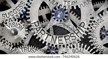 Macro photo of tooth wheel mechanism with Partnership related words imprinted on metal surface #746240626