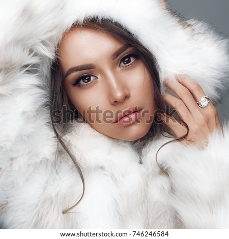 Fashion studio portrait of beautiful lady in white fur coat and fur hat. Winter beauty in luxury. Fashion fur. Beautiful woman in luxury fur coat. Fashion model posing in eco-fur coat and eco-fur hat #746246584