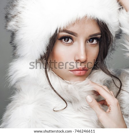 Fashion studio portrait of beautiful lady in white fur coat and fur hat. Winter beauty in luxury. Fashion fur. Beautiful woman in luxury fur coat. Fashion model posing in eco-fur coat and eco-fur hat #746246611