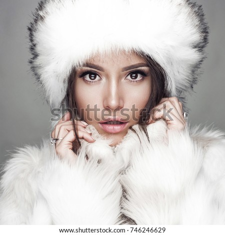 Fashion studio portrait of beautiful lady in white fur coat and fur hat. Winter beauty in luxury. Fashion fur. Beautiful woman in luxury fur coat. Fashion model posing in eco-fur coat and eco-fur hat #746246629