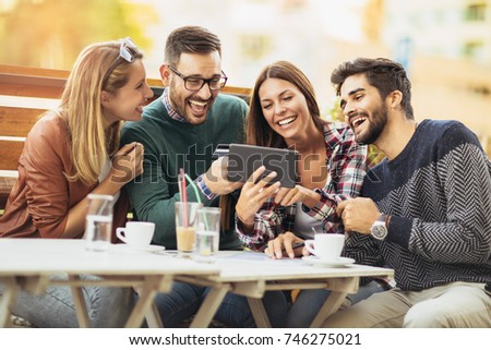 Friends having a coffee together. Two women and two men at cafe shopping on line with digital tablet #746275021