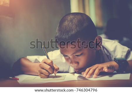Asian rural student Interest readiness fluency working textbook At desk is writing learning and process teaching in classroom rural thailand assessment Intellect primary school basic education #746304796