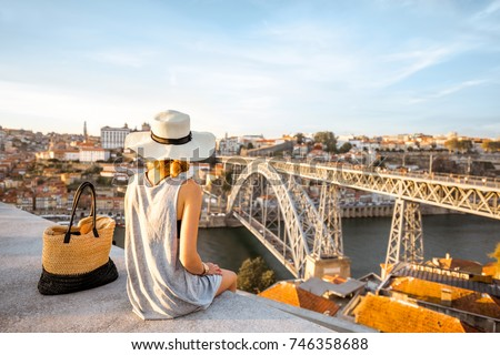 Young woman tourist enjoying beautiful landscape view on the old town with river and famous iron bridge during the sunset in Porto city, Portugal #746358688