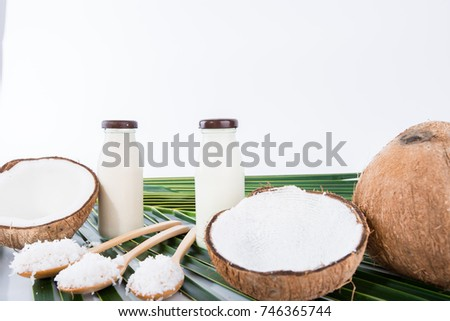coconut milk in bottles and fresh coconut on green leaves , white background with copy space #746365744