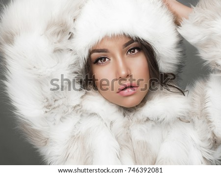 Fashion studio portrait of beautiful lady in white fur coat and fur hat. Winter beauty in luxury. Fashion fur. Beautiful woman in luxury fur coat. Fashion model posing in eco-fur coat and eco-fur hat #746392081