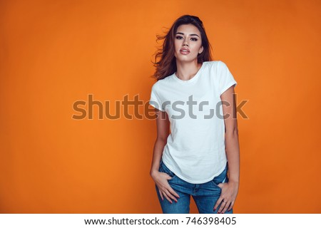 Sexy woman in a white T-shirt on the orange background. Mock-up. #746398405