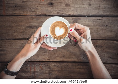 hands holding coffee cup,heart on coffee cup and woman nails,valentine love concept.