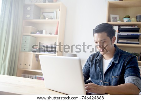 The Asian Man with blue jeans jacket using computer or tablet  #746424868