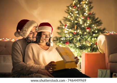 Sweet couple opening Christmas gifts, sitting in the living room #746449969