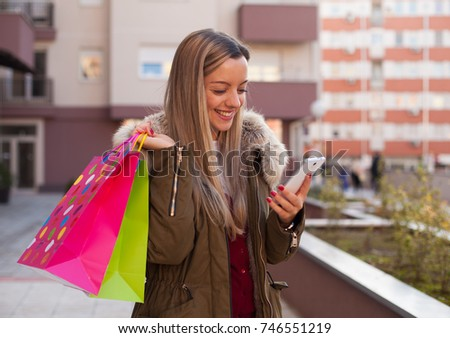 Happy young woman holding shopping bags and looking on smart phone #746551219