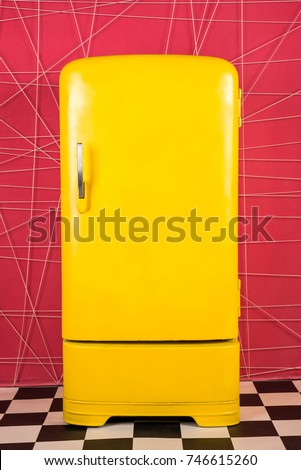 old vintage yellow refrigerator on a pink background #746615260