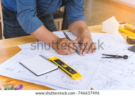 Engineer man working with drawings inspection in workplace in office .Engineering tools and construction concept. architect and Business concept. #746637496