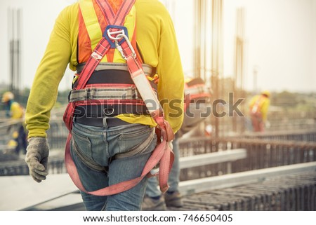 Working at height equipment. Fall arrestor device for worker with hooks for safety body harness on selective focus. Worker as a background. Royalty-Free Stock Photo #746650405