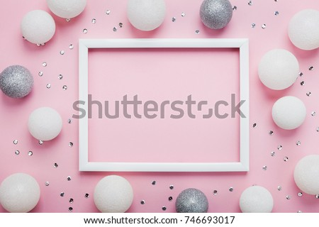 Christmas balls, sequins and picture frame on stylish pink table top view. Fashion background. Flat lay. Party mockup or invitation.