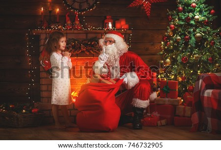 Merry Christmas! santa claus and little child girl at night at the Christmas tree #746732905