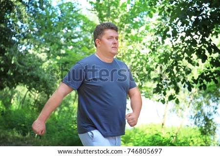 Overweight man running in green park #746805697