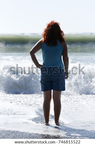 A red headed woman in blue denim shorts and a sleeveless turquoise top looks out towards crashing waves in the sea. #746815522
