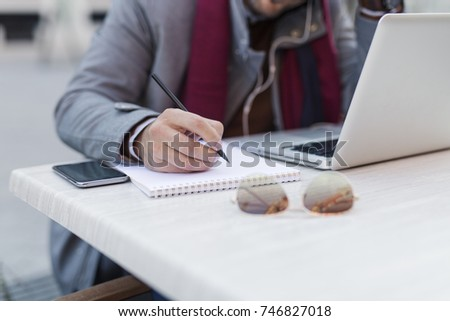 Businessman writing something on paper. Close up #746827018