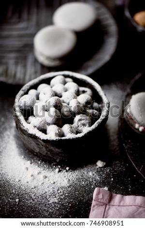The photo in the dark gray scheme. Grey cake macaron. Macro. Blueberries, which rolled in powdered sugar.