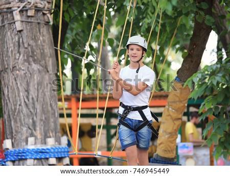 Cute boy climbing in adventure park #746945449
