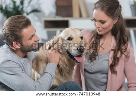 Man and woman playing with their dog at home in living room #747013948