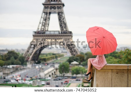 Girl in pink dress with red umbrella sitting on the roof top of the Trocadero place in Paris and looking at the Eiffel tower