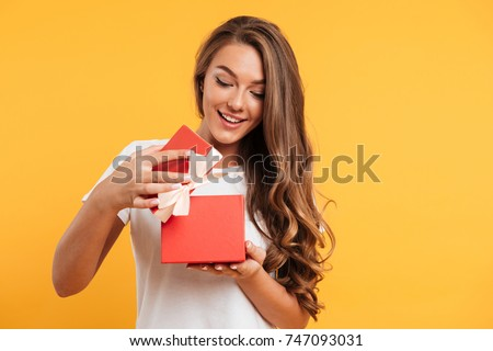 Portrait of a happy smiling girl opening a gift box isolated over yellow background #747093031
