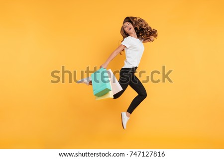 Image of laughing pretty young woman jumping isolated over yellow wall background. Looking aside holding shopping bags. #747127816