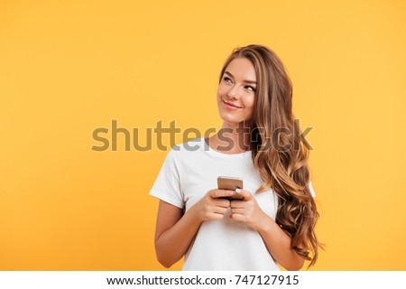 Photo of cheerful cute beautiful young woman chatting by mobile phone isolated over yellow wall background. Looking aside. Royalty-Free Stock Photo #747127915