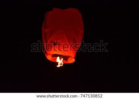 Floating lantern on dark black night sky in mid-air #747130852