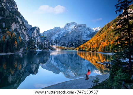 A woman and a dog standing on the shore of a beautiful alpine lake #747130957