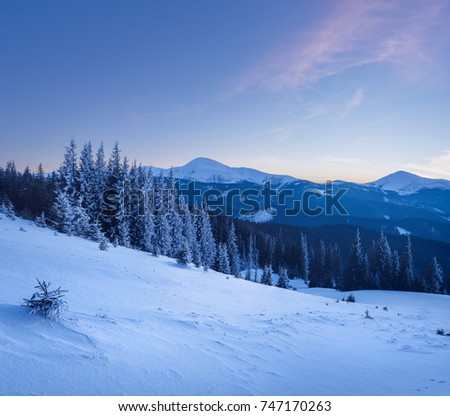 Sunset at mountains in winter. Landscape of mountains and forest covered with snow at sunset. Mountain range at the background. #747170263