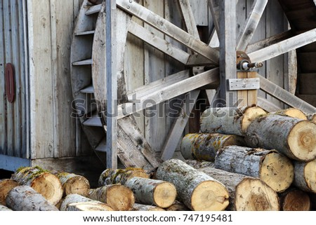 A giant wooden water wheel and cut logs next to a cabin #747195481