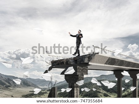 Businessman walking blindfolded among flying paper planes on concrete bridge with huge gap as symbol of hidden threats and risks. Skyscape and nature view on background. 3D rendering. #747355684