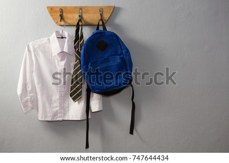 School uniform and schoolbag hanging on hook against wall Royalty-Free Stock Photo #747644434