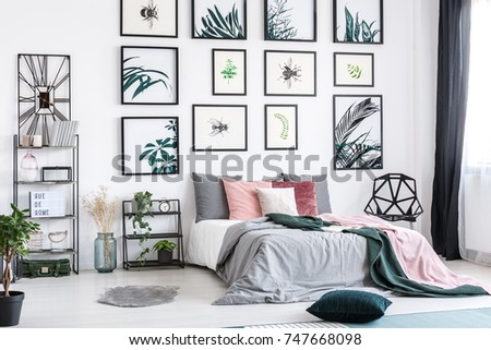 Designer clock on shelf in cozy bedroom with posters above king-size bed with pink and green bedsheets #747668098