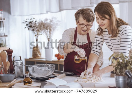 Grandmother helping her granddaughter make dough by adding olive oil #747689029