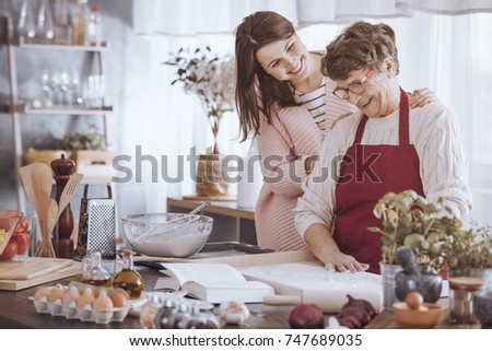 Smiling woman massaging grandmother's shoulder while making cake in the kitchen #747689035