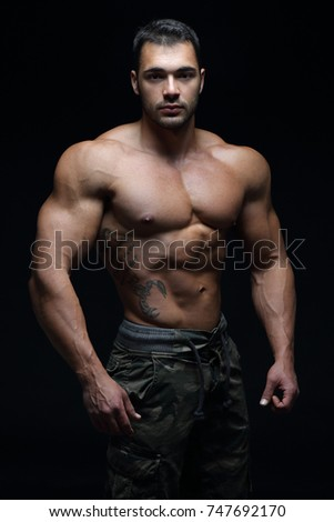Handsome guy posing in front of black background #747692170