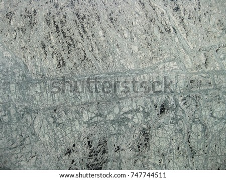 An intricate web of green and black veining in a polished granite surface  #747744511