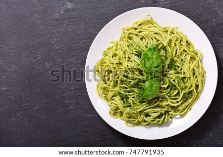 plate of pasta with pesto sauce on dark background, top view #747791935