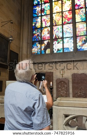 Prague, Czech Republic - 17 August 2017: Elderly couple looking up the stained glass window by Alphonse Mucha. Woman takes photo with mobile phone, St Vitus Cathedral in Prague. #747825916
