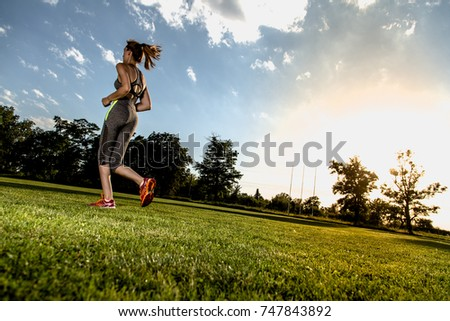 Wide angle picture of running women with sun in background #747843892
