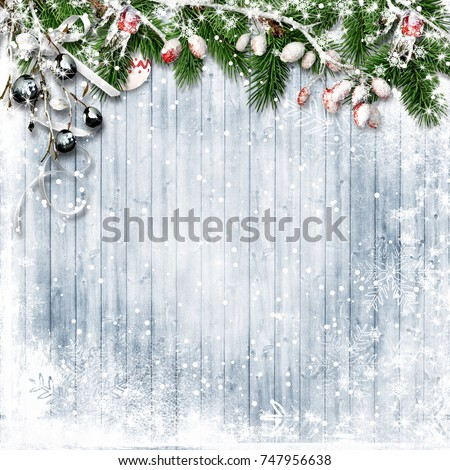 Christmas firtree with holly, snowfall on wooden white board