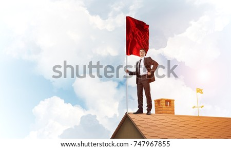 Businessman standing on house roof and holding red flag. Mixed media #747967855