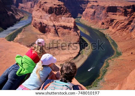 Young man and two girls laying on the edge of the cliff. Horse Horseshoe Band Canyon. Adventure and tourism concept  #748010197
